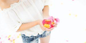 両手で花びらを持っている女性