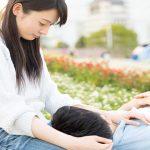 公園で膝枕をするカップル