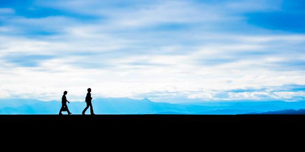 まっすぐな道を歩く2人