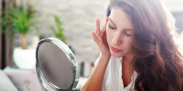 手鏡を見つめる女性