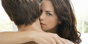 女性が男性と抱き合いながらこちらを見ている写真
