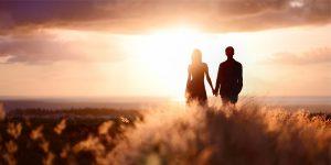 夕日の海を見ながら手をつなぐ男女