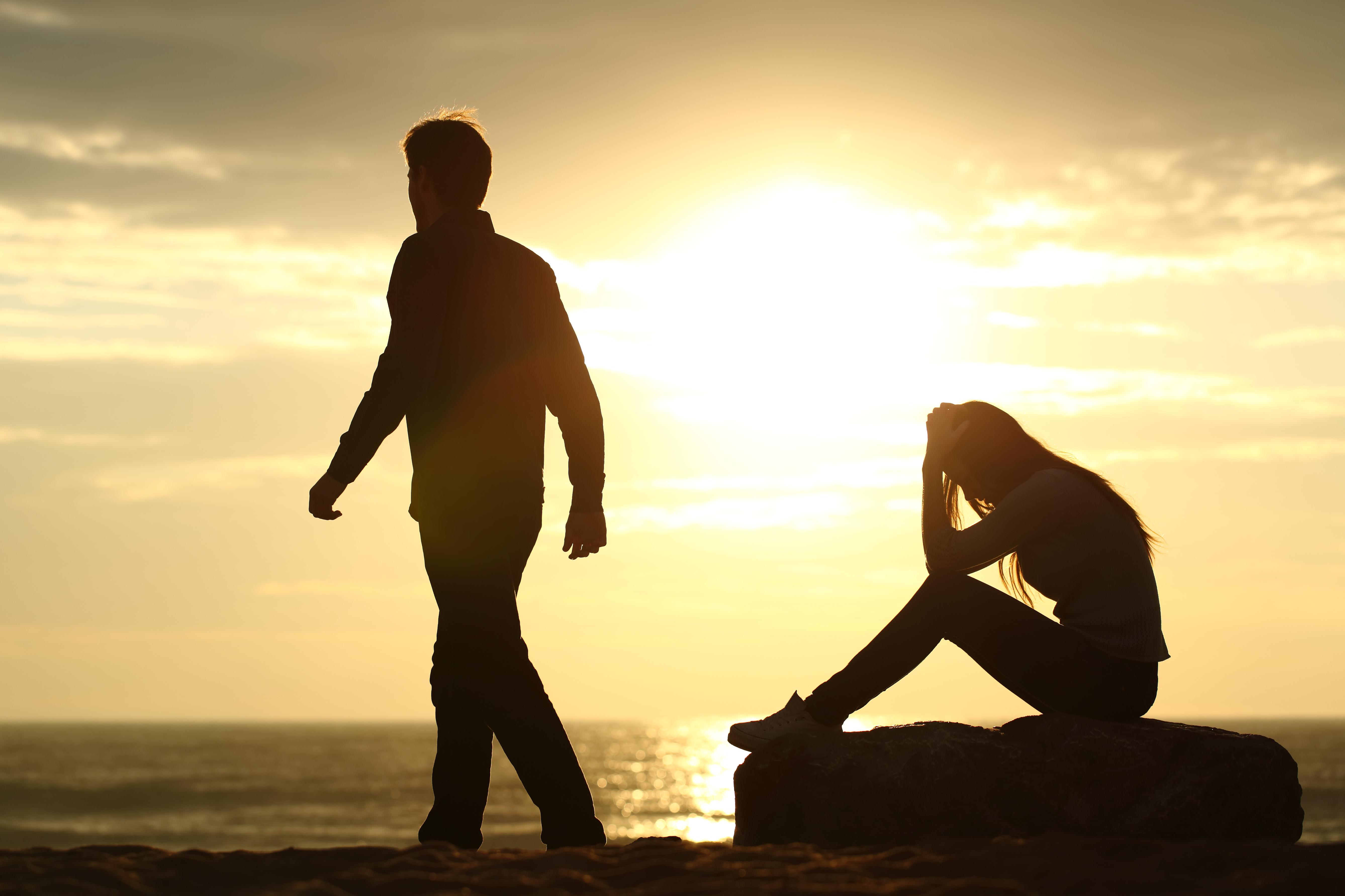 夕日の海で別れる男女