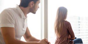 窓際の女性を眺める男性