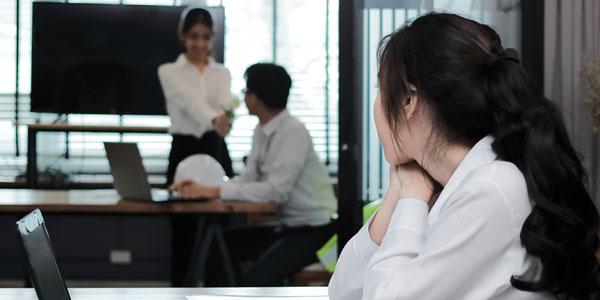 職場で男性を眺める女性