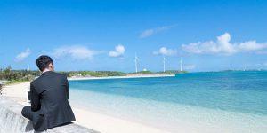 堤防に座りながら海辺を眺める男性