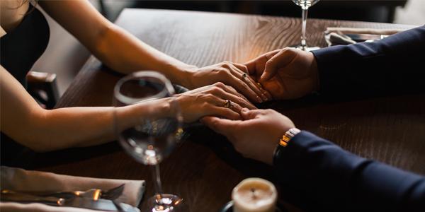 レストランで両手を触れ合う男女