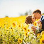 ひまわり畑でキスをするカップル