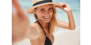海辺でこちらに手を伸ばす水着の女性